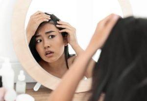 Woman Examining Hair In Mirror